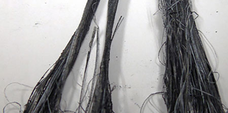 Continuous filament graphite-coated PTFE yarn