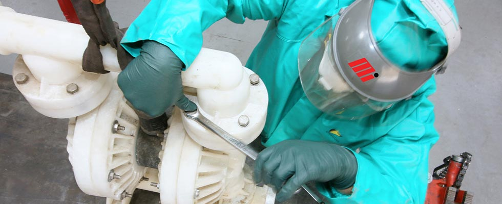 Worker in PPE disassembling an air-operated doule-diaphram (AODD) pump that is pumping hydrochloric acid