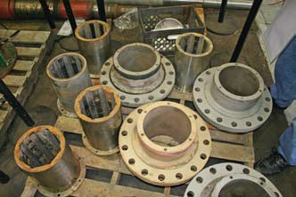 Disassembled flanged bearing housings with failed rubber cutlass bearings remove