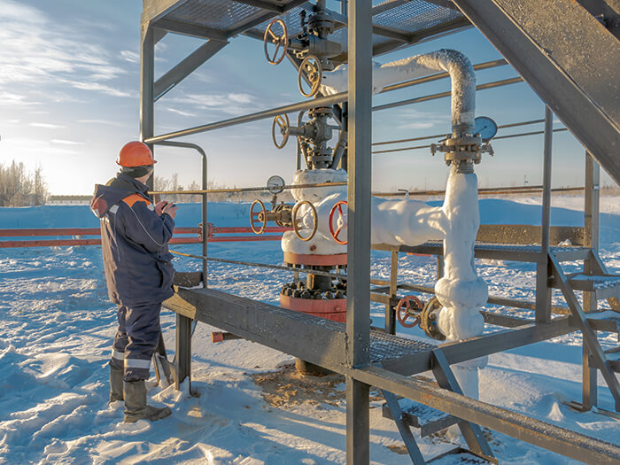An operator services an oil well in the northern oil field in winter