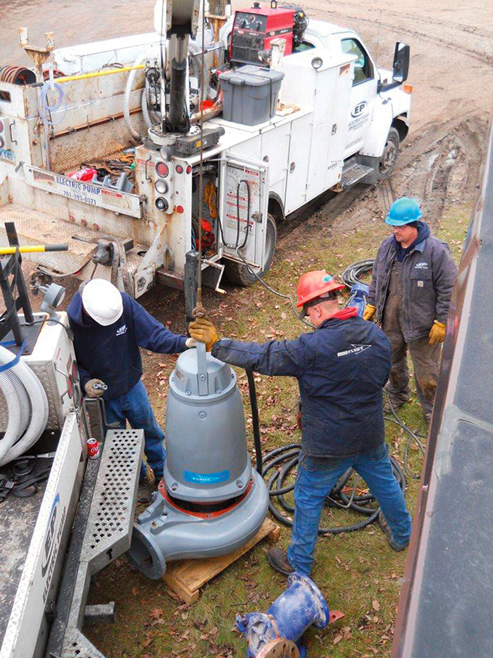 A three-man crew uncrates and prepares the new pump for installation after piping modifications.