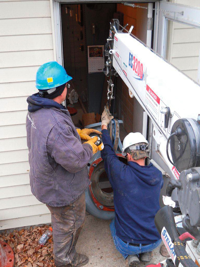 The crew maneuvers and lowers the volute for the replacement pump through the side door into the station.