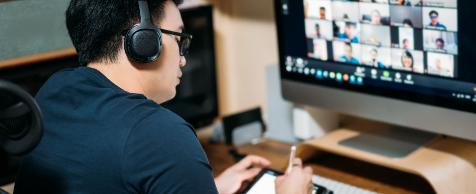 man at computer with headset looking at zoom call on screen